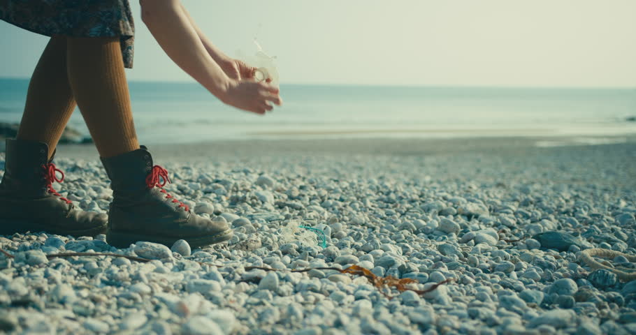 A young woman is cleaning up the beach and picking up plastic rubbish and other manmade waste | Shutterstock HD Video #1028463494