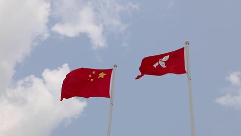 National flag of People's republic of China and regional flag of Hong Kong Special Administrative region, with white clouds and blue sky in background