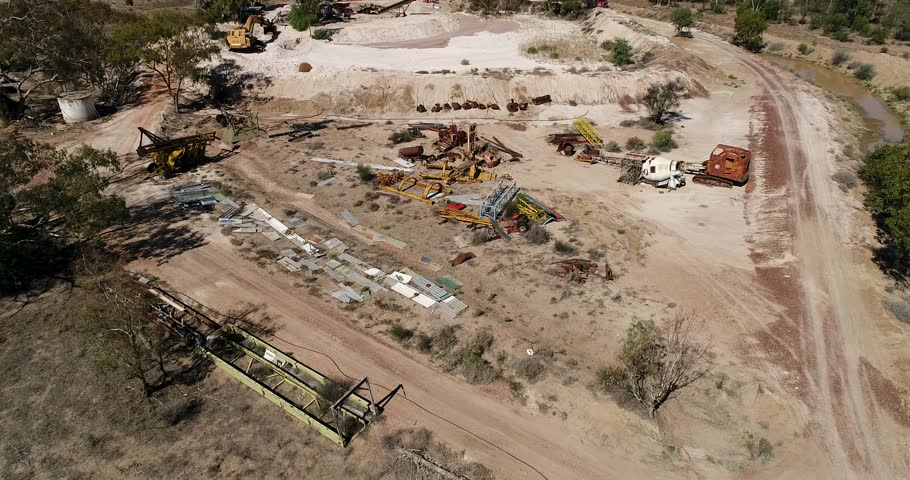 Scrap yard of old rusty machinery, vehicles, excavators, tractors, cabins in old abandoned opal mine around Lightning ridge town of outback Australia.