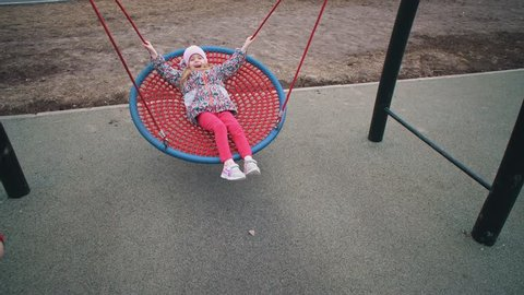 Little cute girl swinging on round swing with tight weave rope platform seat in park on cloudy day.