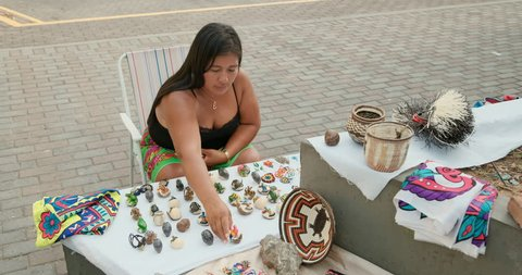 Indigenous woman of Kuna Indians from Darién or Darien province, Panama selling handmade handicrafts, objects in Panama City. Lady of Central American tribe with tourist souvenirs in market shop