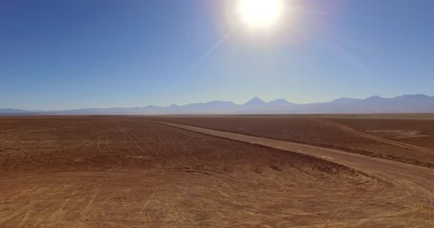 SALAR DE TARA, ATACAMA DESERT, CHILE - JUNE 2016. Red SUV drive along the empty road of the wasteland. An extraterrestrial scene of the unique Atacama desert.
