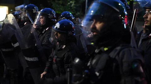 Italian Police officers in full riot gear look on with batons and shields during a far-right demonstration at night in Milan, Italy on April 29, 2019