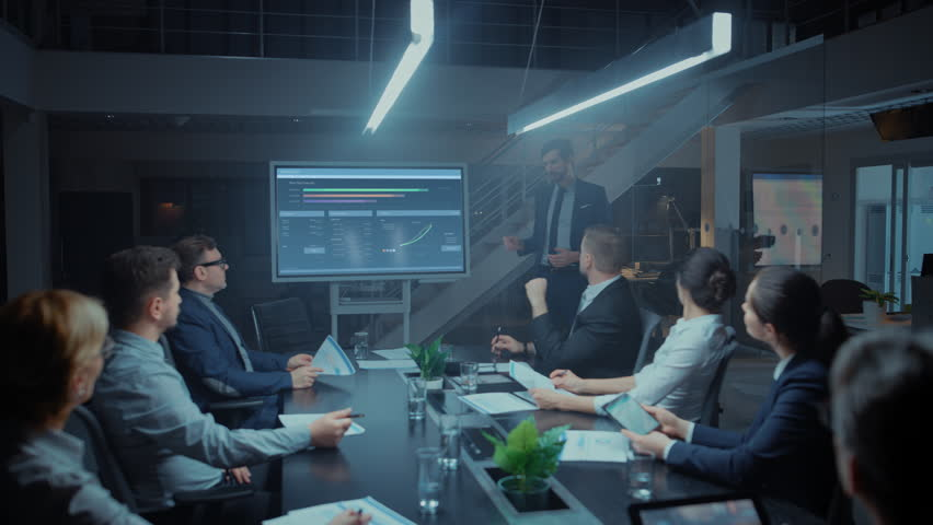 In the Corporate Meeting Room: Male Executive Talks and Uses Digital Interactive Whiteboard for Presentation to a Board of Directors, Investors. Screen Shows Growth Data. Late at Night Office | Shutterstock HD Video #1028612204