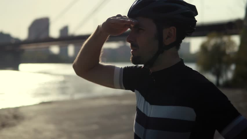 Cyclist In Helmet Looks At The Horizon.Bicyclist Looking For A Way.Cyclist Looking At The Distance.Cyclist Man Looks Around.Bicyclist Are Looking At Road.Cyclist Looking For His Friends. Biker Looks. #1028623334