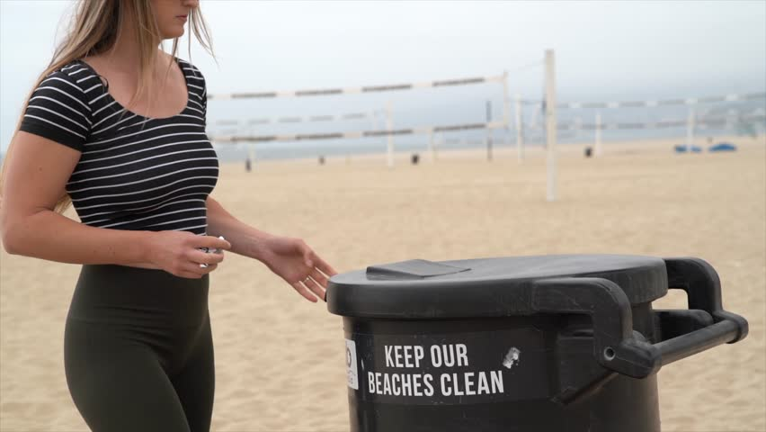This slow motion video shows a young fit caucasian woman throwing away trash at the beach.