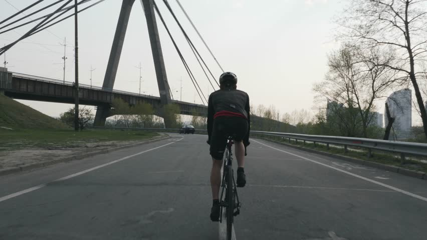 Cycling male. Man on bike. Sportive fit triathlete riding bicycle with bridge on the background. Training for a triathlon race. Triathlon concept. #1028653934