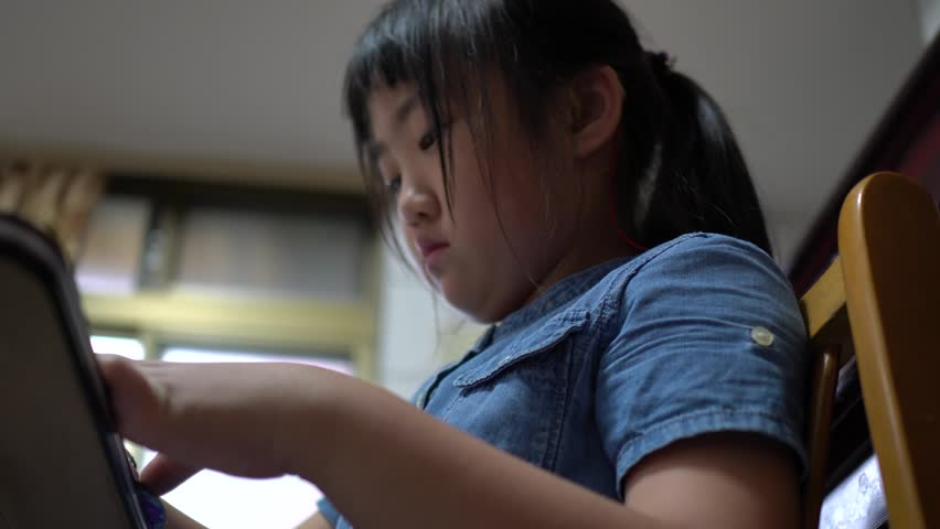 The little girl is painting at home. With hearing aids. | Shutterstock HD Video #1028664254