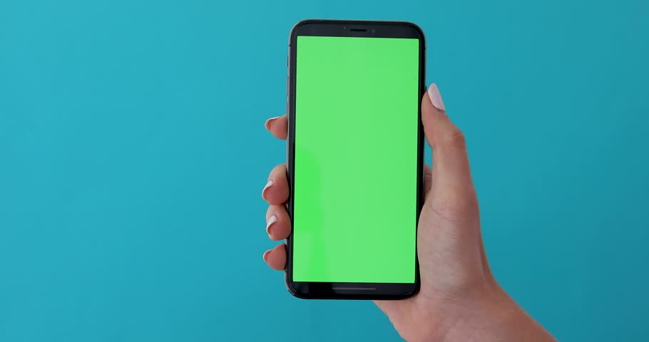 Woman hand holds a smartphone with greeen screen over a blue background. Close up footage of hand only   Shutterstock HD Video #1028678714
