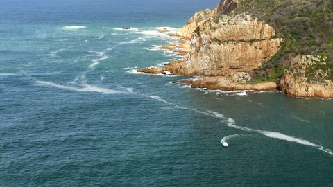 High angle of blue water river mouth, rocky cliffs to ocean shoreline  and a small power boat circling & moving towards POV, white lines of foam on water surface, sunny, Knysna, South Africa