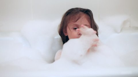 Adorable bath baby girl plays with soap