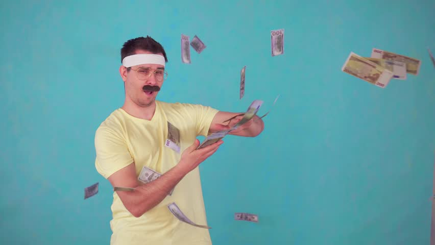 A cheerful man with a mustache looks at the camera and throws a pack of money | Shutterstock HD Video #1028724584