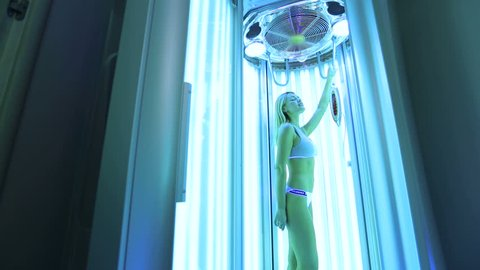 Beautiful and athletic girl in a white bathing suit sunbathing in the solarium. Portrait of a gorgeous slender girl in the Solarium, she stands under ultraviolet rays and sunbathes.