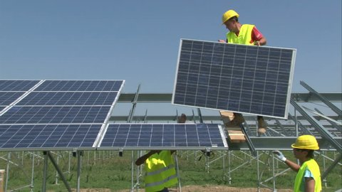 Workers are mounting panels on solar power-plant construction.