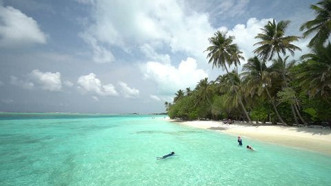 Maldives Indian Ocean White Coral Sand Beach With Tropical Vegetation and People Snorkelling on Cloudy Summer Day