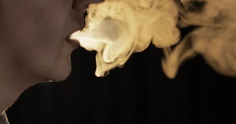 Handsome, young man smoking hookah. Attractive guy smoking flavored tobacco. Blow out smoke close-up on black background