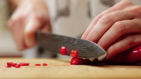 Close up view of female hand chopping with a knife on cutting board red hot chili pepper. Cutting red hot pepper on cutting board. Hand using knife to slice, chop chilli pepper for cooking