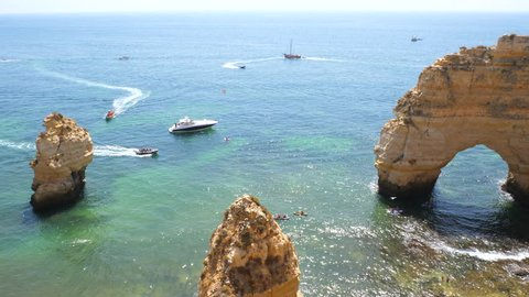 Multiple ships and boats and kayaks between the natural arc and cliffs of Praia da Marinha in Portugal