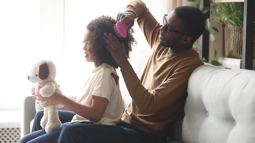 Loving black father doing brushing afro hair of cute little kid daughter talking bonding sitting on sofa at home, caring single african dad babysitter helping child girl with hairstyle in the morning