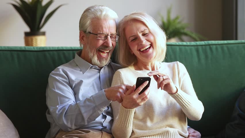 Happy old mature retired couple holding smartphone looking at cellphone screen laugh watching funny photos sit on sofa, cheerful senior family having fun enjoy read online news in smartphone at home
