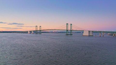 Aerial drone shot of Delaware Memorial Bridge at dusk. The Delaware Memorial Bridge is a set of twin suspension bridges crossing the Delaware River between the states of Delaware and New Jersey