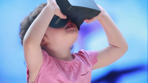 Virtual reality game. The little girl with surprise and pleasure uses head-mounted display.