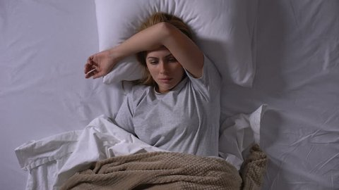 Sad lady lying in bed suffering from intestinal flu feeling nausea and dizziness