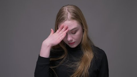 Closeup portrait of young attractive brunette female clapping her head with a hand with embarrassment and annoyance with background isolated on gray