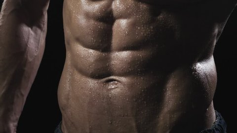 Muscle man torso. Close-up man showing a perfect abs. Man posing on a black background, shows his muscles.The concept of bodybuilding
