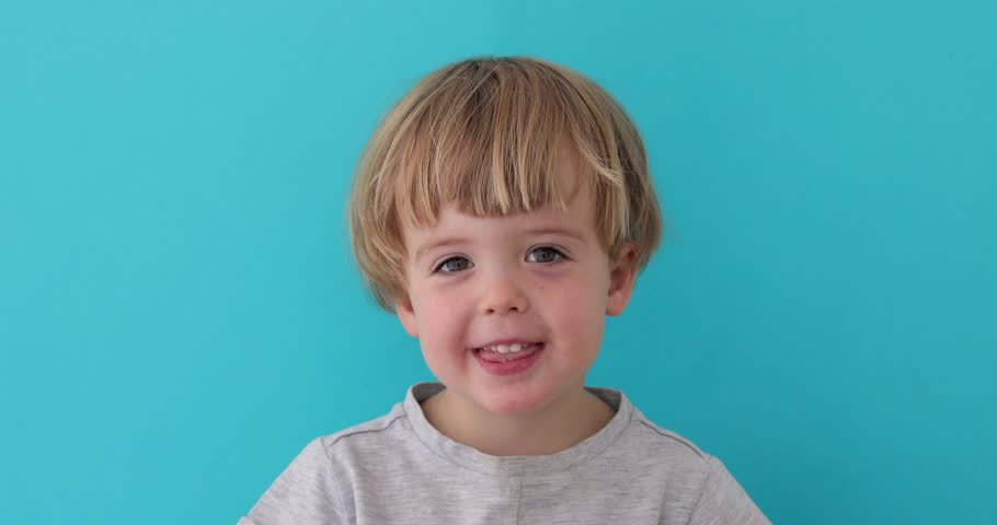 Little boy laughing at camera on blue background #1028958884