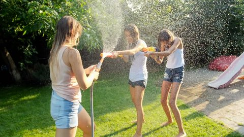 Slow motion footage of cheerful young family with children playing with water guns and water hose in garden at hot summer day
