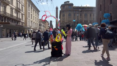 BOLOGNA, ITALY - MAY 1, 2019: A balloon artist works from her stall on a busy street during May Day celebrations in Bologna, Emilia-Romagna, Italy.