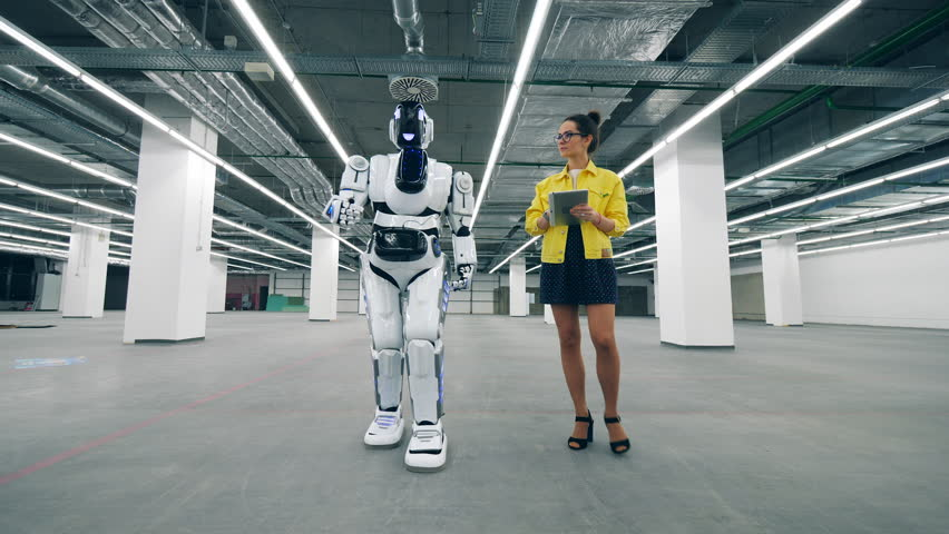 Young woman with a tablet switches on a cyborg | Shutterstock HD Video #1028988314