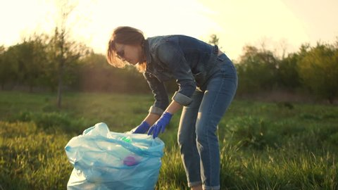 Active woman cleans the park of debris, folding it in a blue plastic bag, it takes the package in his hands and goes out of the frame. The work of environmental volunteer