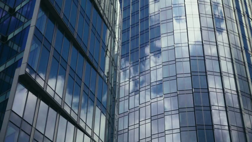 Modern Business Office Buildings with Glass Reflection. Time lapse of clouds reflecting onto the glass of a large office building. Reflection of clouds in a modern skyscraper.