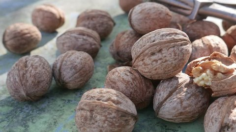 Kernel nut, cracked and whole walnut on old green desk in sunny day. Healthy snack food