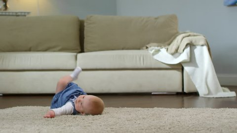 Full shot of adorable Caucasian baby girl crawling on all fours on carpet in living room at home, trying to stand up but falling on her back, then rolling over to crawl again