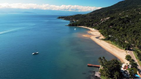 Aerial: Gorgeous Blue Water and Rich Green Jungle Along Coastline in Ilhabela, Brazil