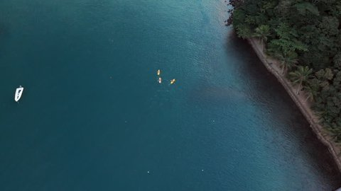 Aerial: Three People Kayaking in Vibrant Tropical Water Near Coast in Ilhabela, Brazil