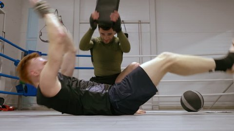 Personal training of professional boxer making adominal exercise with his  trainer laying on ringside and lifting his body and legs  fighter hits  partner to stomach of sparrer