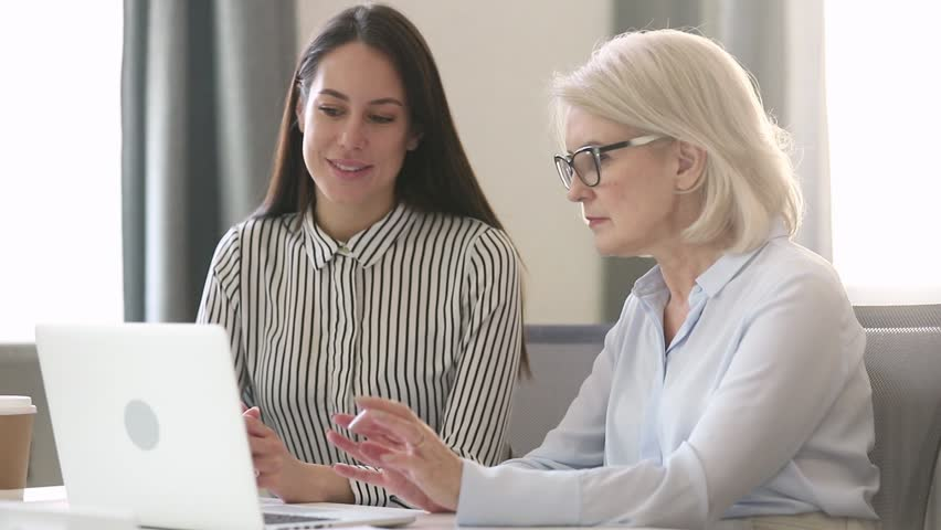 Older female professional mentor teach young intern worker learn new skill look at laptop, mature businesswoman executive manager explain colleague computer work talk consult client with computer | Shutterstock HD Video #1029051434