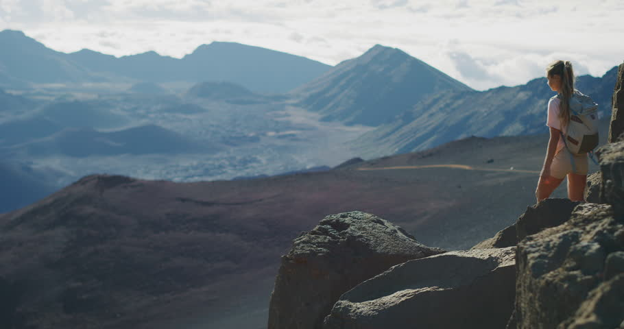 Young adventurous woman leaps onto a rock in slow motion and enjoys the view from the top of a mountain with her arms raised in joy, amazing summer adventures | Shutterstock HD Video #1029056114