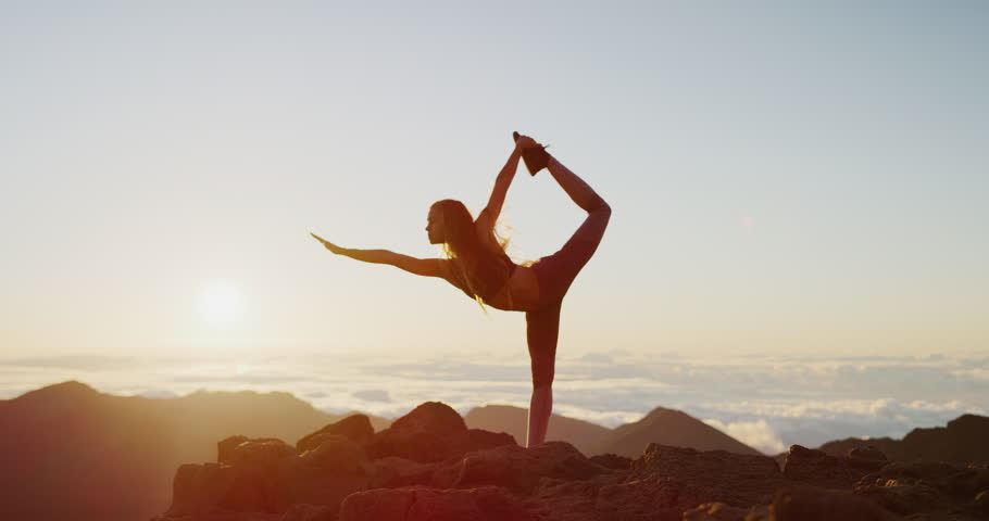 Young athletic woman performing yoga pose on the top of a mountain at sunrise, zen wellness woman performs dancer's pose | Shutterstock HD Video #1029056204