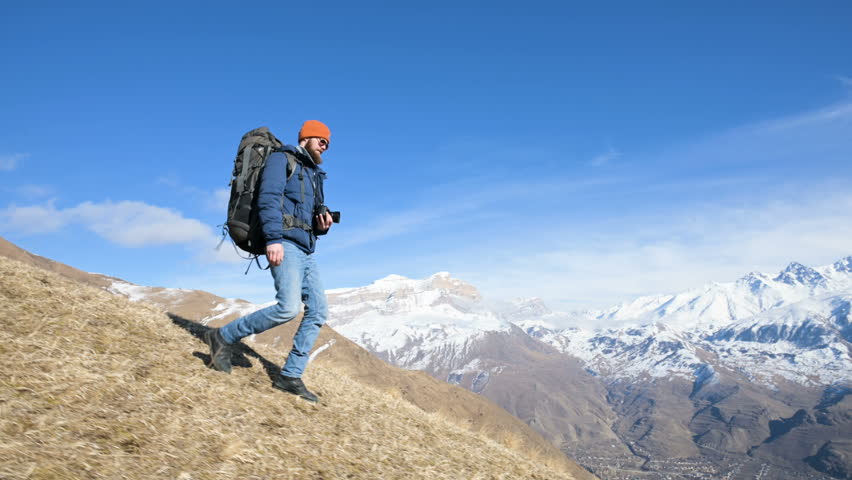 Bearded young male photographer in a hat and sunglasses with a large backpack and a camera around his neck coming down the hill from a mountain against the backdrop of snow-capped mountains