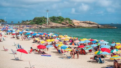 Rio de Janeiro, Brazil - January 12, 2019: Time lapse view of Ipanema Beach showing colourful umbrellas and people enjoying the beach on a summer day in Rio de Janeiro, Brazil.