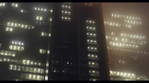 Looking upwards at corporate skyscraper with moving elevators into a foggy sky at night. Looks dystopian, cyberpunk, gothic and neo noir like in Blade Runner movie.