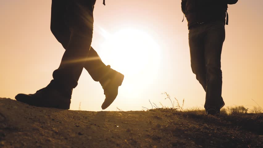 teamwork business travel concept. legs silhouette group hikers of people walking on the top of the mountain with backpacks sunset sun light . slow motion video. campaign lifestyle tourists with #1029114734
