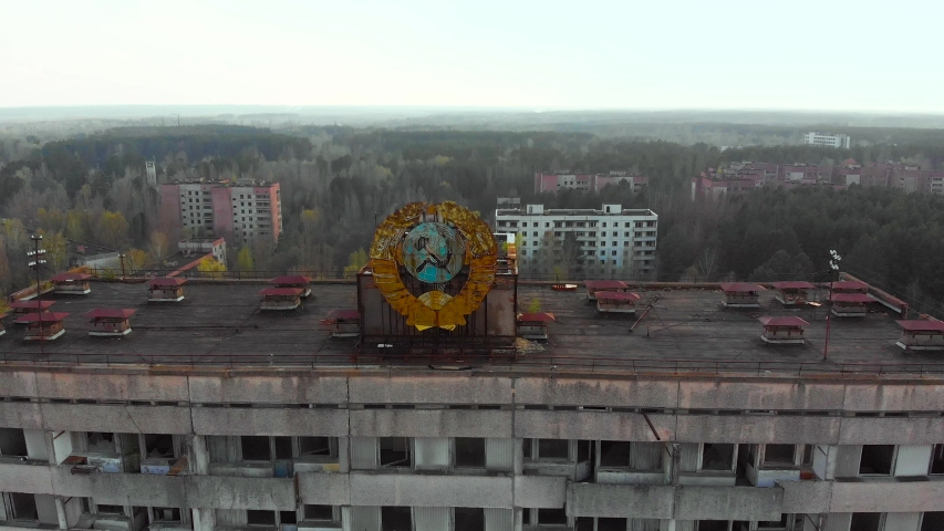 Pripyat aerial panorama cityview over the sign of USSR on the roof of building. Soviet coat of arms on a high-rise building in Pripyat, view from above. | Shutterstock HD Video #1029156704