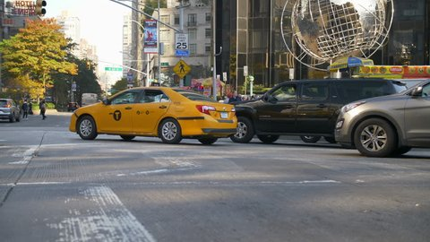 NEW YORK CITY, USA - 03/06/2019:  Armillary Sphere At Trump International Hotel And Tower In Columbus Circle. New York city traffic at rush hour. classic yellow Taxi Cab. Sunny Day.