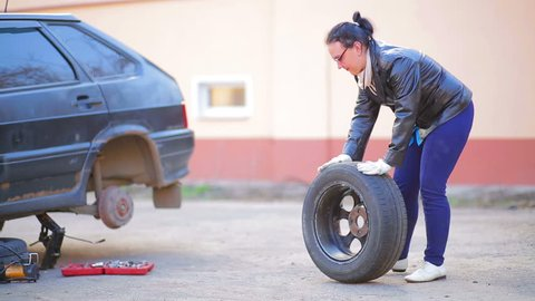 A woman in gloves puts a tire on a disk on the axle of a car